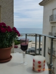 Glass of wine in the sunshine on the balcony over looking the sea