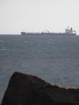 A cargo ship against a grey sky and sea